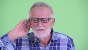 Любопытный старший бородатый человек хипстера слушая акции видеоматериалы