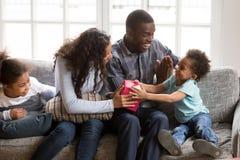 Любящая африканская семья сидя на кресле дома стоковое фото