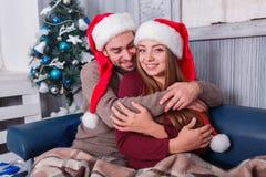 Любящая и счастливая пара нежно обнимает пока сидящ на софе indoors стоковое изображение