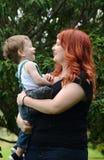 Любящая мать держа сына младенца малыша смеясь над совместно outdoors стоковое фото