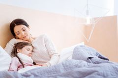 Любящая мать обнимая ее больного спать ребенка Стоковые Изображения RF