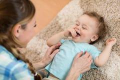 Любящая мать щекоча ее маленький ребенка на ковре дома стоковое фото rf