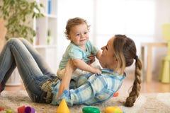 Любящая мать щекоча ее маленький ребенка на ковре дома стоковая фотография
