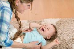 Любящая мать щекоча ее маленький ребенка на ковре дома стоковая фотография rf