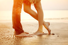 Любящая молодая пара обнимая и целуя на пляже на заходе солнца