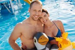 Любящая пара в заплыве звенит представлять в бассейне стоковая фотография