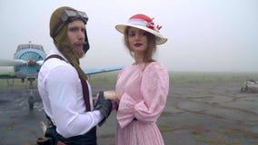 Любящая пара в костюмах шестидесятых лет пилота и женщины стоит перед старым самолетом и смотрит в сток-видео