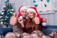 Любящая пара в крышках рождества сидит на кресле и показывает большой палец руки вверх indoors стоковые фотографии rf