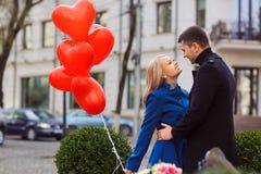 Любящая пара в пальто с сердцами воздушных шаров в руках на cit Стоковые Фото