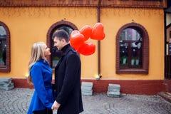 Любящая пара в пальто с сердцами воздушных шаров в руках на cit Стоковое Изображение RF