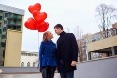 Любящая пара в пальто с сердцами воздушных шаров в руках на cit Стоковое фото RF
