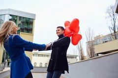 Любящая пара в пальто с сердцами воздушных шаров в руках на cit Стоковая Фотография RF