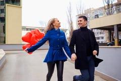 Любящая пара в пальто с сердцами воздушных шаров в руках на cit Стоковые Изображения