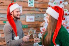 Любящая пара в рождестве покрывает приветственные восклицания с шампанским и милый взгляд на одине другого indoors стоковое фото