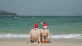 Любящая пара в шляпах ` s Санты сидит на пляже южного пляжа видеоматериал