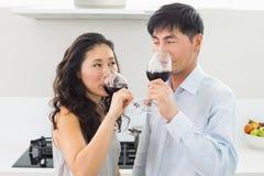 Любящие молодые пары выпивая красное вино в кухне стоковые фото