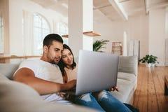 Любящие молодые пары используя компьтер-книжку дома Стоковые Изображения