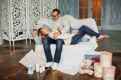 Любящие молодые пары ослабляя на софе, смеясь над Стоковое Изображение