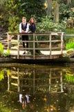 Любящие пары в викторианской моде около озера с отражениями в парке Стоковое Изображение