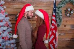 Любящие пары в красных крышках эльфа, одине другого взгляда в глазах, стоя близко к одину другого indoors стоковое изображение