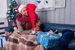 Любящие пары в красных крышках эльфа плотно обнимают indoors стоковая фотография rf