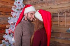 Любящие пары в крышках рождества, усмехаясь и смотря один другого indoors стоковые фото