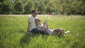 Любящие пары в солнечных очках на заходе солнца прочитали книгу на поле с одуванчиками сток-видео