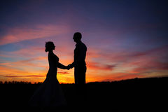 Любящие пары держа руки на заходе солнца Стоковое фото RF