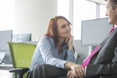 Любящие пары дела смотря один другого в офисе Стоковые Фото