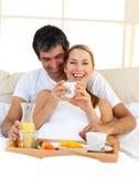 Любящие пары имея завтрак лежать в кровати Стоковые Изображения