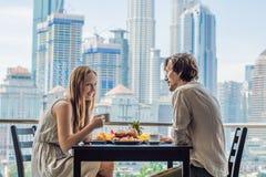 Любящие пары имея завтрак на балконе Таблица завтрака с плодом и хлебом кофе croisant на балконе против стоковая фотография rf