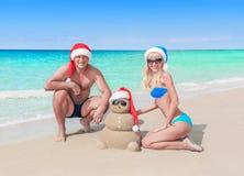 Любящие пары и смешной песочный снеговик рождества в шляпах santa на море приставают к берегу Стоковая Фотография RF