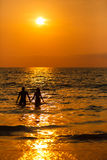 Любящие пары на заходе солнца в море Стоковые Изображения