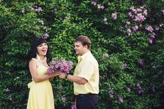 Любящие пары на прогулке в парке в лете Гай дает букет девушки сирени Стоковое Изображение RF