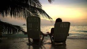 Любящие пары на тропическом пляже восхищают заход солнца и целовать видеоматериал