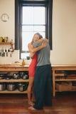 Любящие пары обнимая один другого в кухне Стоковое Фото