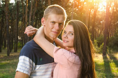 Любящие пары обнимая один другого outdoors на заходе солнца Стоковая Фотография RF