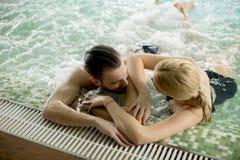 Любящие пары ослабляя на курорте в бассейне Стоковое Изображение