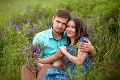 Любящие пары сидя совместно в середине цветков на луге honeymoon стоковое изображение