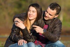 Любящие пары сидя на железной дороге Оба пункта палец Стоковое Изображение RF