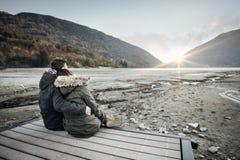 Любящие пары сидя на пристани стоковые изображения