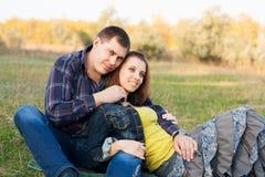 Любящие пары сидя на траве в осени садовничают. Стоковое фото RF