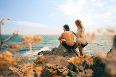 Любящие пары смотря заход солнца на береге моря Свободный полет Чёрного моря Стоковое Изображение
