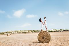 Любящие пары стоя на стоге сена и усмехаясь друг к другу стоковые изображения rf