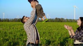 Любящие родители играют с их ребенком на поле Будьте отцом водоворотов сын и мать помогает ему движение медленное сток-видео