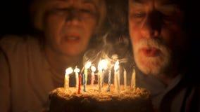 Любящие старшие пары празднуя годовщину с тортом дома в вечере дуя свечки вне сток-видео