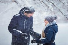 Любящие счастливые пары идя в парк зимы Снежности Стоковая Фотография RF
