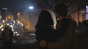 Любящий молодой человек и женщина обнимая нежно, смотрящ романтичный город ночи освещают видеоматериал