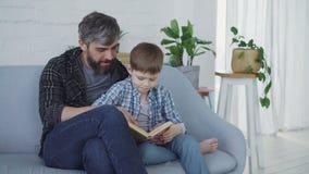 Любящий отец учит, что его маленькому ребенку серьезный preschooler читает пока сидящ совместно на софе зеленые заводы сток-видео
