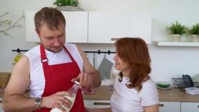 Любящий парень подавая его усмехаясь подруга в их кухне пока делающ завтрак акции видеоматериалы